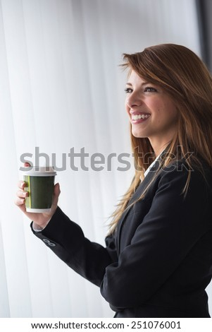 Young cheerful business woman on a coffee break by the office window - stock photo