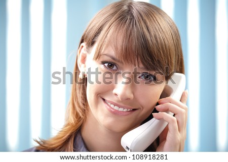 Young cheerful business woman with phone at office - stock photo