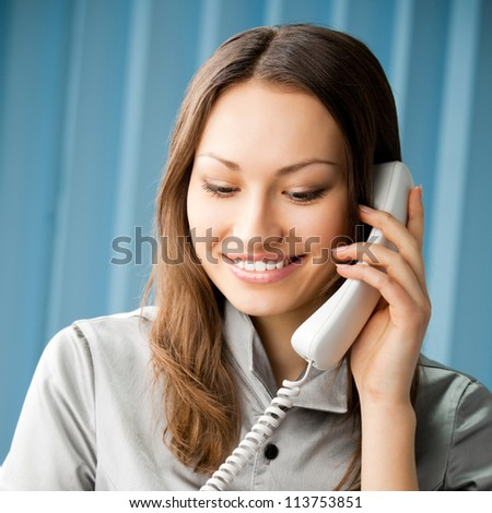 Young cheerful business woman with phone writing at office - stock photo