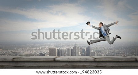 Young cheerful businessman in jump against city background