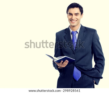 Young cheerful businessman with organizer, with blank copyspace area for slogan or text message - stock photo