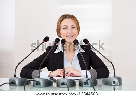 Young Cheerful Businesswoman Giving Speech In Conference - stock photo
