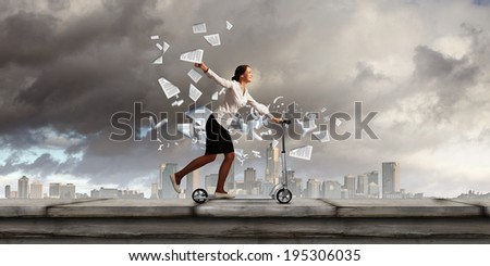 Young cheerful businesswoman riding scooter against city background