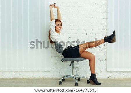 Young cheerful businesswoman sitting on the chair in office - stock photo