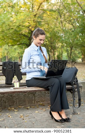 young cheerful businesswoman using laptop on coffee break - stock photo