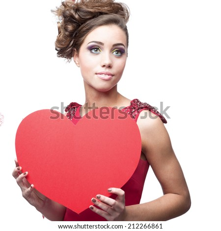 young cheerful caucasian brunette woman in red dress holding big red paper heart - stock photo