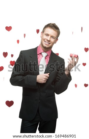 young cheerful caucasian businessman in black suit holding small red gift over flying hearts on background - stock photo