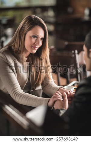 Young cheerful couple at the bar holding hands - stock photo
