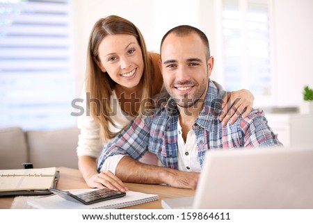 Young cheerful couple calculating savings for home investment - stock photo