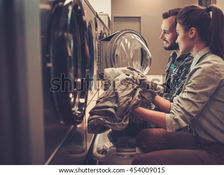 Young cheerful couple doing laundry together at laundromat shop. - stock photo
