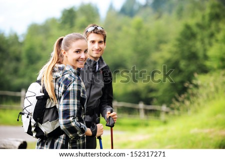 Young cheerful couple enjoying a nordic walk  - stock photo