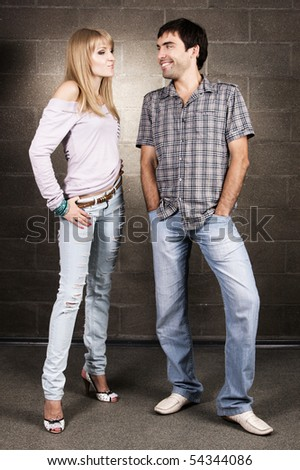 Young cheerful couple on brick wall background - stock photo