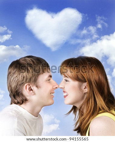 Young cheerful couple on sky background with heart - stock photo