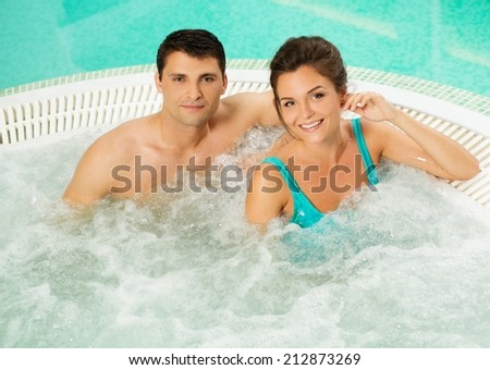 Young cheerful couple relaxing in a jacuzzi - stock photo