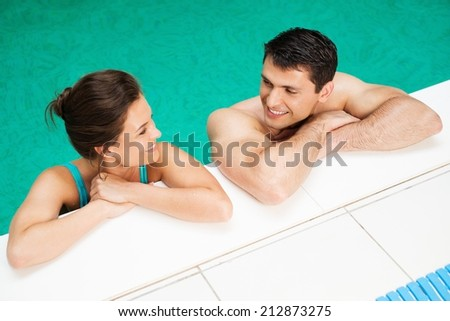 Young cheerful couple relaxing in a swimming pool - stock photo