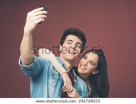 Young cheerful couple taking self pictures with a smart phone - stock photo