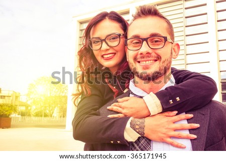 Young cheerful couple with woman embracing man with a positive attitude and smiling face - Happy business people portrait with toothy smile - Concept of happiness friendship and successful life style - stock photo