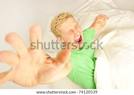 Young cheerful european man in his bed stretching for waking up. Volume perspective shot. - stock photo