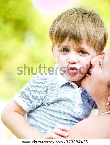 Young cheerful family outdoors. Mother and son - stock photo