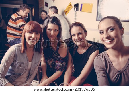 Young Cheerful Female Friends Taking Selfie In Pub - stock photo