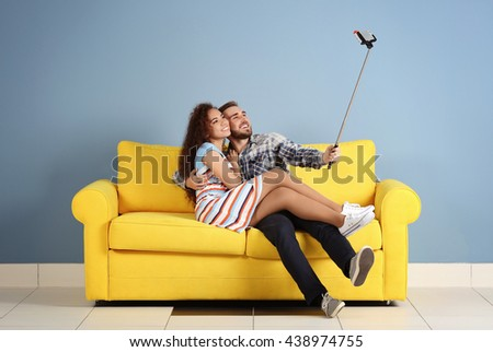 Young cheerful friends taking selfie on yellow sofa in the room - stock photo