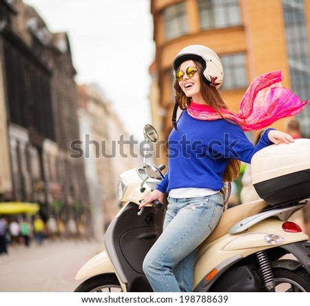 Young cheerful girl driving scooter in in european city  - stock photo