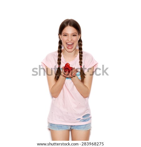 Young cheerful girl having fun and  holding ripe strawberry. Smiling Woman with bright makeup and hairstyle with pigtails. White background not isolated - stock photo
