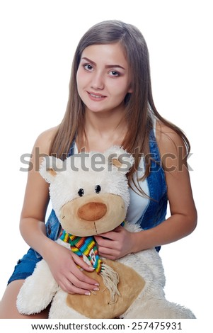 Young cheerful girl holding big soft toy bear isolated on white - stock photo