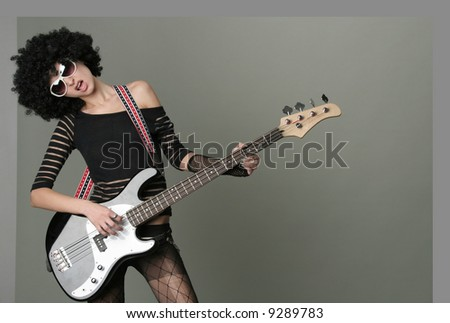 young cheerful girl in a wig plays on a guitar