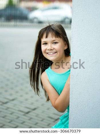 Young cheerful girl is playing outdoors - stock photo