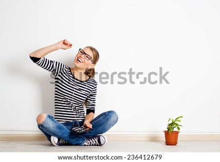 Young cheerful girl listening music in headset sitting on the floor with ipad. Happy Caucasian female wearing stylish jeans and gumshoes singing song.  - stock photo