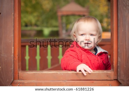 young cheerful girl look through the window in house on playground
