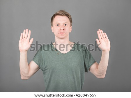 Young cheerful guy holding his hands up isolated on grey background - stock photo