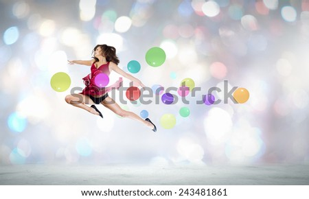 Young cheerful lady in red dress jumping high - stock photo