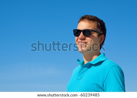 young cheerful man in sunglasses against blue sky - stock photo
