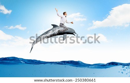 Young cheerful man riding dolphin jumping of water