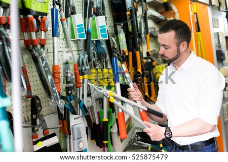 Young cheerful man standing next to shop stall with gardening tools in  household store