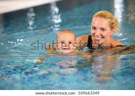 Young cheerful mother and little son enjoying swimming in a swimming pool - stock photo