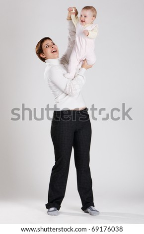 Young cheerful mother exercising her child - stock photo