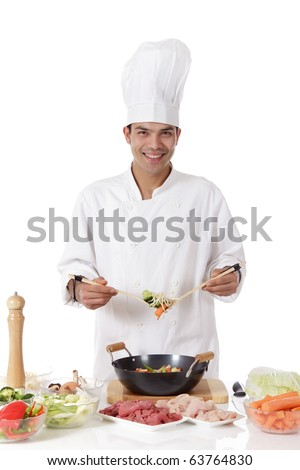 Young cheerful nepalese man chef cooking oriental food in wok. Fresh ingredients on table. Studio shot. White background. - stock photo