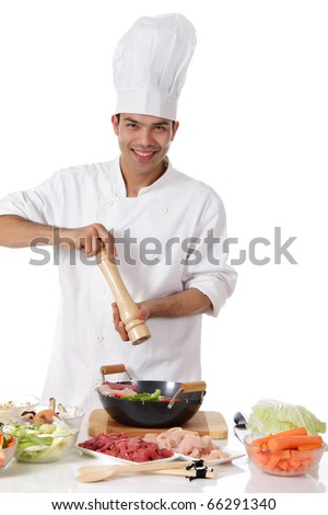 Young cheerful nepalese man chef prepares oriental food in wok, adding pepper. Ingredients on table. Raw meat and fresh vegetables. Studio shot. White background.
