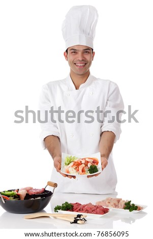 Young cheerful nepalese man showing a plate with oriental food. Wok with ingredients and raw meat on table Studio shot. White background.