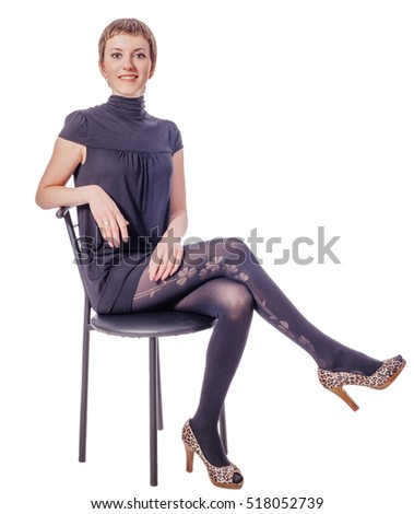 Young cheerful nice woman sitting on chair isolated on white