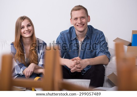 Young cheerful packed couple ready to move out - stock photo