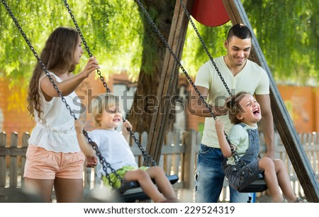 Young cheerful parents with kids at playground's swings. Focus on man  - stock photo