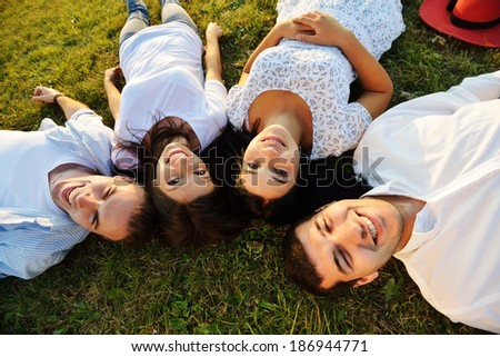 Young cheerful people enjoying on summer meadow