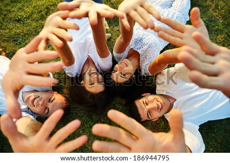 Young cheerful people enjoying on summer meadow - stock photo