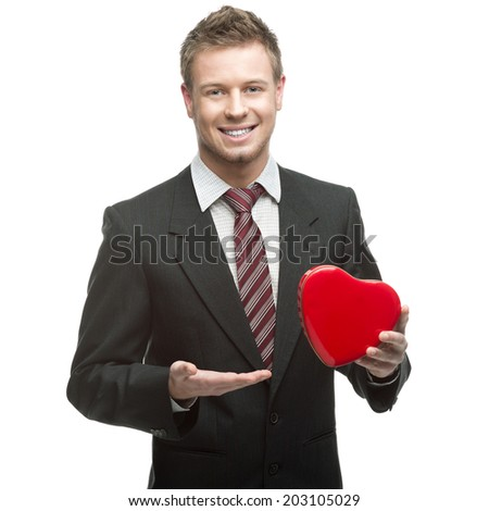 young cheerful smiling caucasian businessman in black suit holding red heart isolated on white - stock photo