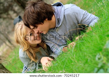 Young cheerful smiling couple laying on the grass in the park - stock photo
