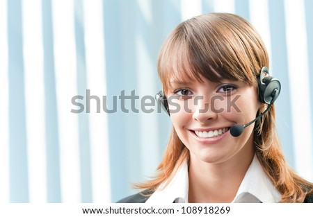 Young cheerful smiling support phone female operator in headset at office, with copyspace - stock photo